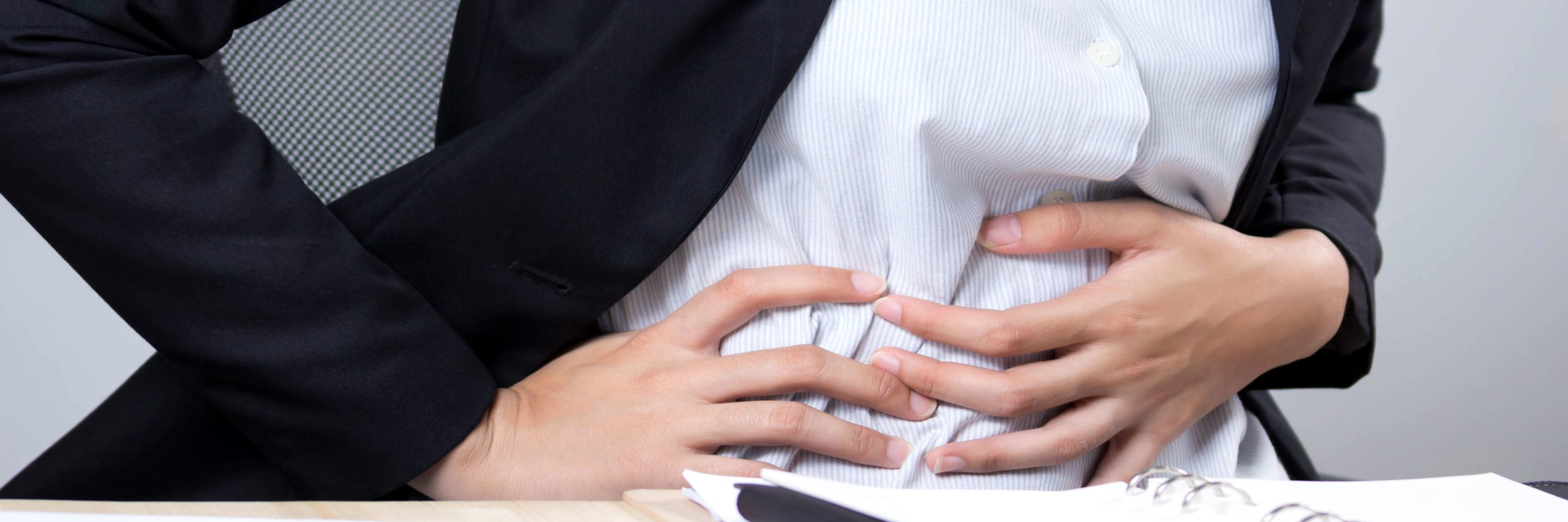 Woman clutches her stomach to portray stomach pain.